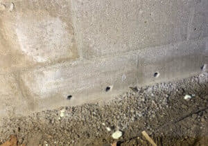 small drainage holes drilled into basement wall