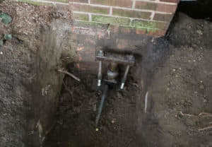 Bracket of helical pier attached to foundation