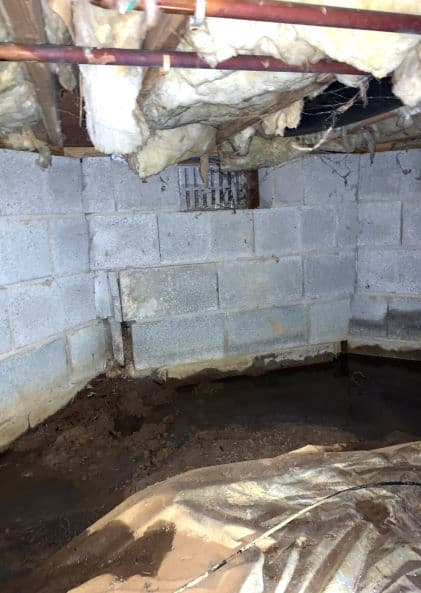 wet crawl space with damage vapor barrier