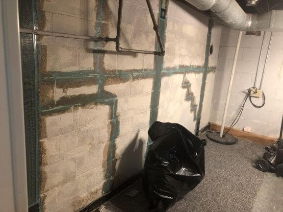 basement wall repaired with straps